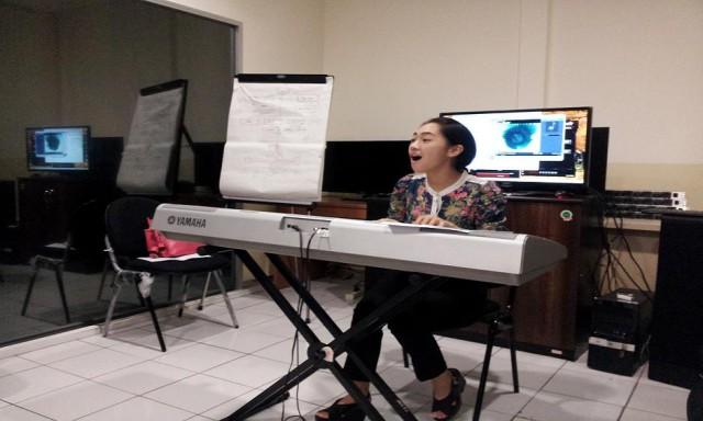 老师一边弹电钢琴一边教学生怎么唱